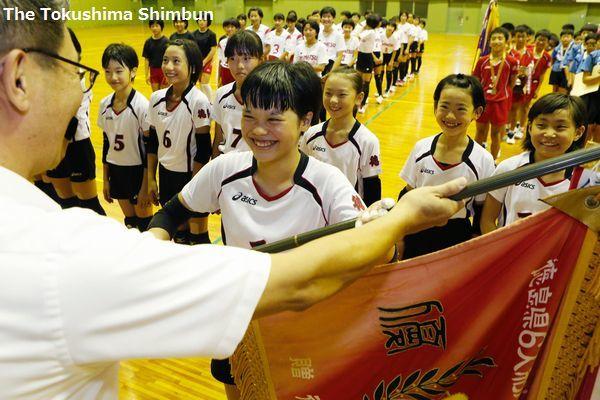 優勝旗を受け取る津田の吉永主将(中央)=小松島市立体育館