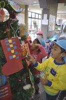 クリスマスツリーを飾り付ける宍喰保育所の園児=海陽町久保の宍喰駅
