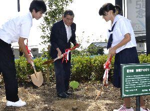 被爆アオギリの苗木を植える野崎市長(中)と中学生=阿波市役所前