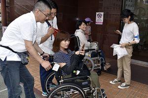 車いすで街を回る参加者=徳島駅前