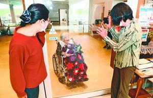 老人ホームに入所する母親(中央)をガラス越しに祝福する家族=徳島市住吉4の仙寿園