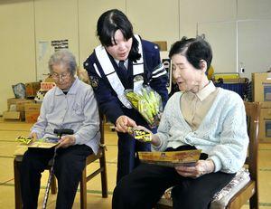 高齢者に反射たすきを手渡す三好署員(中)=東みよし町西庄のデイサービスセンターおおぐす荘