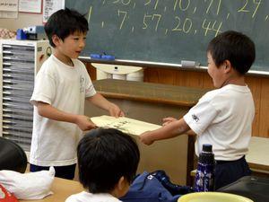 最後の授業を終え、級友(右)から写真を受け取る男児=美波町の日和佐小