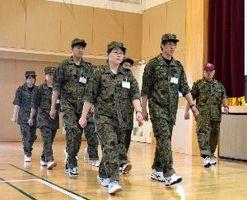 陸上自衛隊員(右端)の指導を受け行進する阿南市の新人職員=同市那賀川町