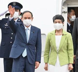 G7サミットを終え英国から帰国し、手を振る菅首相。右は真理子夫人=14日午後、羽田空港