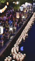 ゆっくりと流れる灯籠を見送る人たち=16日午後7時ごろ、徳島市の新町川