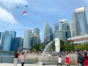 シンガポールの観光名所マーライオン上空で、国旗を掲げて飛行するヘリコプター=9日(共同)