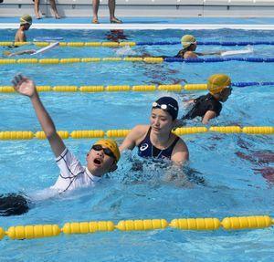 子どもたちに泳ぎ方を指導する中村さん(写真中央)=阿南市那賀川B&G海洋センタープール