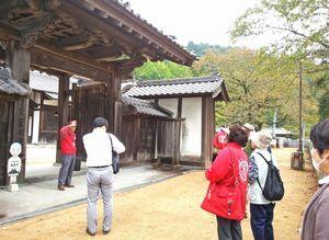 観光客に箸蔵寺を案内する観光ボランティアガイド(左端)=三好市池田町(市観光協会提供)