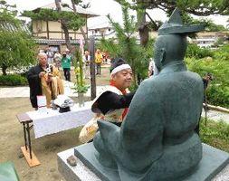三好長慶の銅像を清める「さかい三好まつり」の参加者ら=4日、堺市の南宗寺
