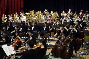 大阪交響楽団と共演する城東小金管バンド部の児童ら(写真奥)=同校