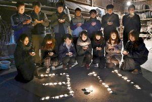 キャンドルをともし、黙とうをささげるダッシュ隊徳島のメンバーら=11日午後9時ごろ、石井町藍畑の山根自動車