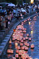 遺族らの手で川面に浮かべられた灯籠=16日午後7時ごろ、徳島市の新町川