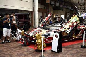 派手なプリントが施された痛車を眺めるアニメファン=徳島市の東新町商店街