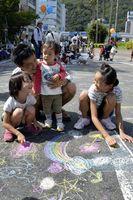 路面にチョークで思い思いの絵を描く子どもたち=徳島市新町橋1