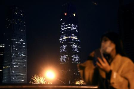 明かりが少ないオフィスビルに点灯した「感染症との戦争に勝利」という趣旨のスローガン=3月26日、北京(共同)