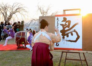 和太鼓の演奏に合わせ、書の実演を行う吉野さん=吉野川市鴨島町の向麻山公園