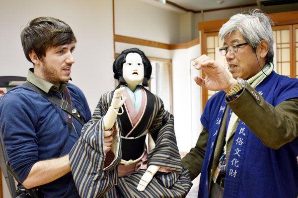 人形の操り方を教わるリッチさん(左)=徳島市の阿波十郎兵衛屋敷