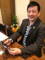 スマートフォンでニュースを確認する長坂さん。判決は「大きな一歩」と語る=徳島市内