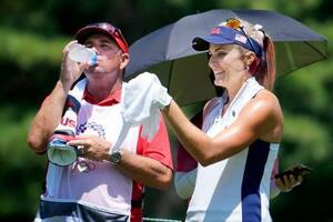 女子ゴルフの第1ラウンドで、水分を補給するL・トンプソンのキャディー(左)。この後、熱中症でダウンし、医務室に運ばれた=霞ケ関CC