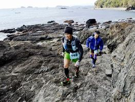 海岸沿いの険しい岩場を走る選手=牟岐町灘
