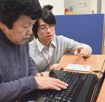 平間さん(写真手前)にパソコンの操作方法を手ほどきする阪井さん=徳島市の視聴覚障がい者支援センター