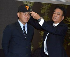 巨人と仮契約を結び、表情を緩める折下(左)=徳島市のJRホテルクレメント徳島