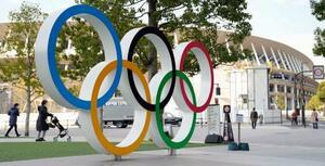 国立競技場(奥)と五輪マークのモニュメント=22日午後、東京都新宿区