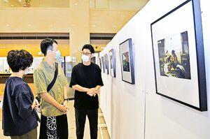 大杉隼平さん(右端)から話を聞きながら写真に見入る来院者=鳴門市撫養町黒崎の県鳴門病院