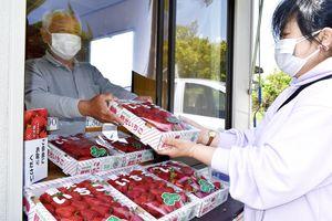 旬を迎えたイチゴを買い求める客(右)=阿波市土成町の直売所