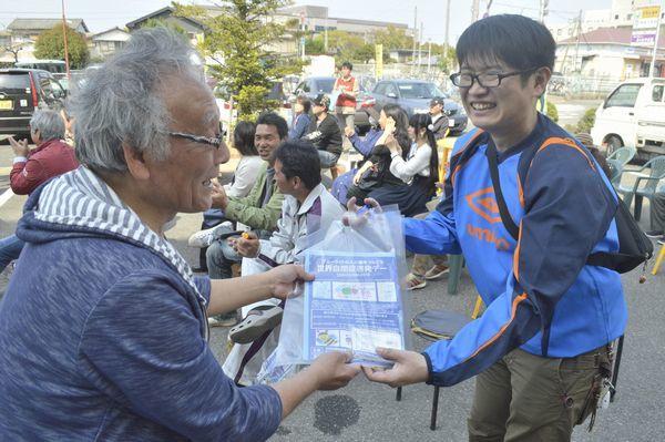 住民㊧に啓発リーフレットを手渡す「かもっこ」の会員ー吉野川市鴨島町の鴨島駅前