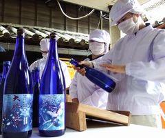 「大地の夢」のラベルを瓶に貼る三好高校生=三好市池田町サラダの三芳菊酒造
