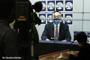 リモート中継で臨時記者会見を行う飯泉知事=17日午後5時45分ごろ、徳島県庁