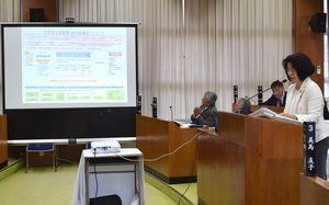 スクリーンを使って説明する美馬議員(右)=勝浦町役場内の町議会議場