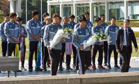 広島市の平和記念公園を訪れ、原爆慰霊碑へ献花するサッカー男子U―22日本代表の中山雄太選手(手前左)ら。後列左から2人目は久保建英選手=13日