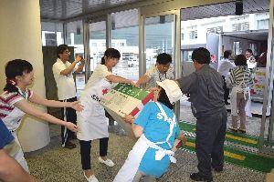 日赤から届いた支援物資を運ぶ町職員ら=那賀町和食郷の鷲敷体育館