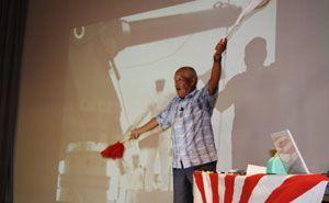 伝令に使う旗を手に、戦艦大和の乗務について語る石上さん=小松島市立江町黒岩のふれあいセンター立江