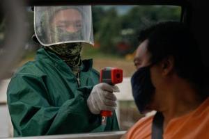 検疫チェックポイントで、フェースシールドをつけて通行者の検温をする地元警察官=5日、マニラ首都圏ケソン市(ロイター=共同)