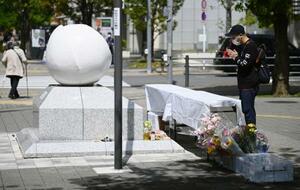 東京・池袋の乗用車暴走事故から2年となり、現場近くの慰霊碑に向かって手を合わせる男性=19日午前