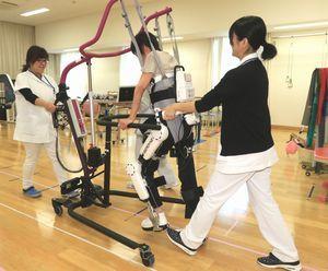 医療用ロボットスーツを使って歩行訓練を行う患者(中央)=吉野川市鴨島町の徳島病院