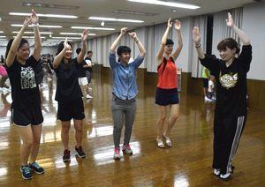 連員から女踊りの指導を受ける留学生=阿南市富岡町の市文化会館