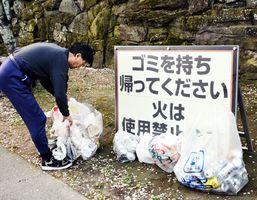 花見客が放置したごみを拾い集める男性=2日午前5時50分ごろ、徳島市徳島町城内の徳島中央公園