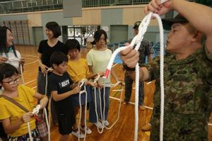学校主催の防災イベントでロープワークを学ぶ児童(左側)=8月、阿南市の津乃峰小学校体育館