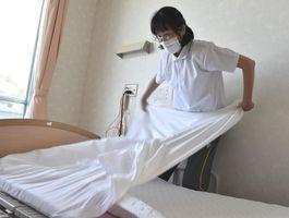 利用者のベッドのシーツ交換をする介護助手の大原さん=徳島市の特別養護老人ホーム・かもな園