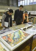 空襲体験を描いた絵画や焼夷(しょうい)弾の破片などを見学する来場者=徳島市の徳島大常三島キャンパス