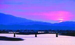 夕焼けに染まる空と川面に浮かぶ那賀川鉄橋=阿南市那賀川町