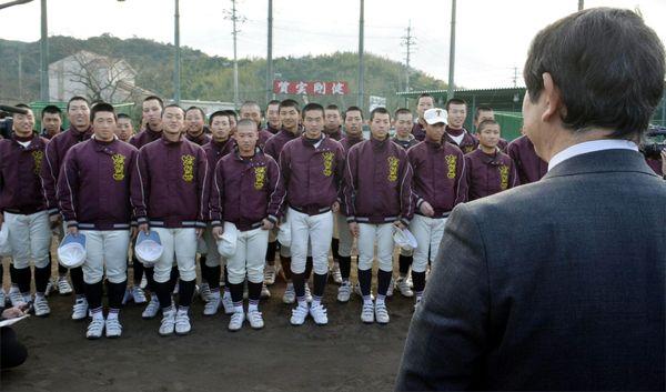 グラウンドで吉田校長から21世紀枠での選抜出場決定の吉報を聞く富岡西の選手たち=1月25日