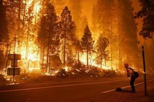 2020年9月、米西部カリフォルニア州フレズノ近郊の山火事現場に立つ消防士。米国では熱波の影響で山火事が増加傾向にある(AP=共同)