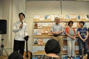 ギター曲の印象を描いたデッサンの前で参加者に語り掛ける徳永真一郎さん(左端)=上板町の技の館