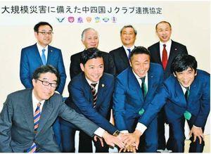 大規模災害時の連携協定を締結し記念撮影する、中四国を本拠地とするサッカーJリーグの7クラブ代表ら。後列左端が徳島ヴォルティスの冨本常務取締役=岡山市